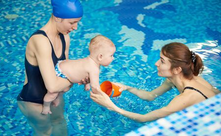 Little child accustoming to water at first lesson in pool. Woman entertain and amuse baby to not afraid swimming. Side view. Active family spending leisure and time in spa fitness recreational center
