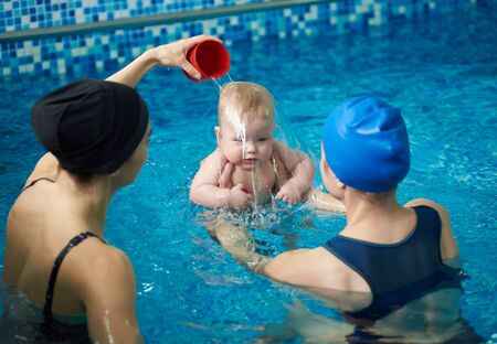 Front view of baby boy during swimming lesson. Back view of mother holding child and woman pouring water on childs head, accustoming his to water. Formation of hardiness and endurance in infants Banco de Imagens