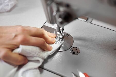 Seamstress hand stitching white fabric on professional machine at workplace. Footplate of sewing machine holding fabric down onto the part that feeds it under needle. Close up view. Blurred background