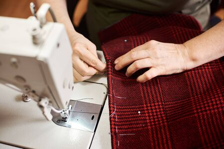 Top view of preparing process before sewing plaid red fabric. Clothier female hands fixing, fitting edges of plaid textile with pins, threads. Close up top view. Blurred background with sewing machine