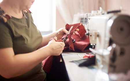 Side view of woman, laboring at working place. Female hand using scissors for cutting off textile piece in sewing process. Blurred background. Handicraft, hobby, self-employment, business concept. Stock Photo