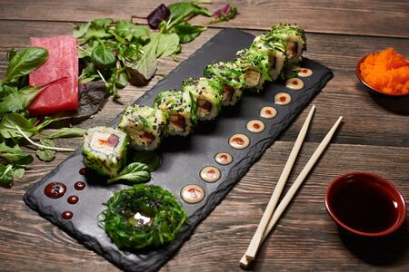 Japanese rolls on stone plate cooking of rice, raw fish, serving with seaweeds, black sesame seeds and sauce drops. Tuna piece on mix salad, bamboo chopsticks, caviar, soy sauce on wooden dark table.