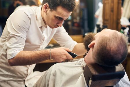 Professional hardworking barber standing near his client sitting in hairdresser chair. Close up view of beard shaving process. Business, service, masculine style, hair care, barbershop concept