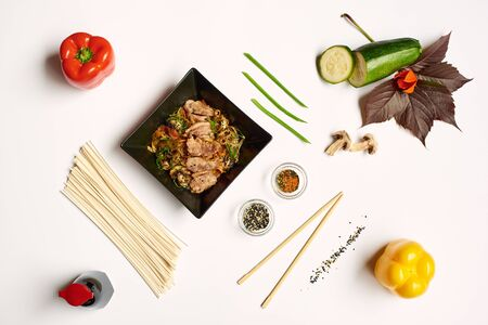 Close up of still life on white tablecloth from above. Composition from food and colorful vegetables. Noodles with meet in center decorated with seeds, red and yellow peppers, soya sous and zucchini.