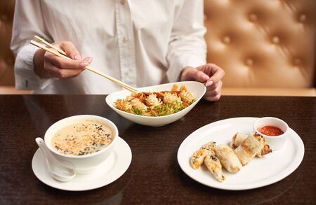 Woman in white blouse sitting in luxury restaurant and eating tasty meal. Three courses lunch from soup, noodles and tempura shrimps on special offer. Girl with manicure tasting oriental style dish.