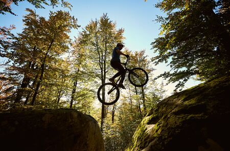 Young male cyclist jumping on trial bicycle between two big boulders, professional rider making acrobatic trick in the forest on sunny day. Concept of extreme sport active lifestyle