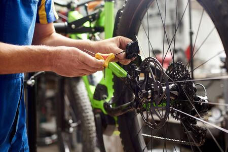 Cropped shot of male mechanic making service in bicycle repair shop, repairing modern bike brakes using special tool, wearing protective workwear