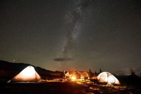 Three tourist tents on mountain valley and group of four people, young men and woman with guitar by burning bonfire on background of dark sky with bright sparkling stars and Milky Way constellation. 版權商用圖片