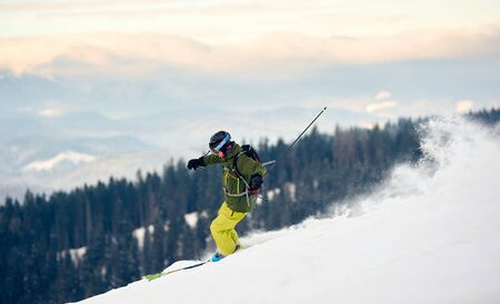 Proficient skier with backpack racing down from high slope. Concept of popular winter extreme amateur sport. Active lifestyle in winter. Amazing nature mountains view from high ski slope. Side view 版權商用圖片