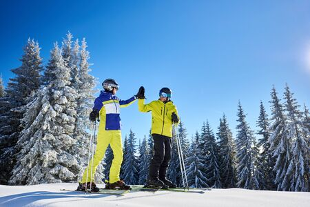 Couple skiers man and woman giving high five to each other after successful downhill skiing on snow-covered mountain slope. Snowy coniferous forest on winter sunny day on background. Stock Photo