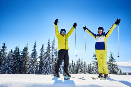 Smiling couple of skiers in goggles with reflection, posing on skis with ski poles in hands up on snow-covered wooded mountain top. Happiness, goal achievement concept. Clear blue sky with copy space.