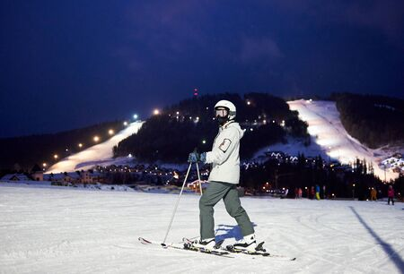 Woman skier in ski mask, goggles standing on skis under dark blue night sky, turning back, looking in camera. Ski resort landscape with street lighting on background. Popular winter vacation concept