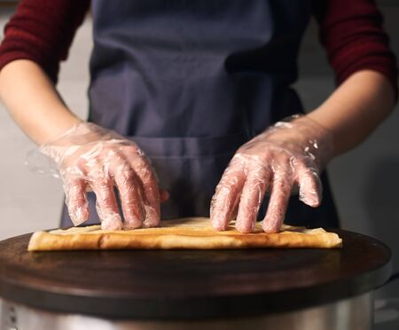 Cropped view of professional cook in apron while baking crepe process on hot round cooktop. Skillful hands in gloves rolling up fried crepe. Traditional restaurant healthy food. Close up. Front view. Stock Photo