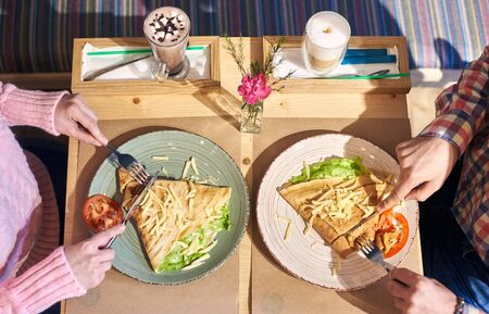 Cropped hands of man and woman savoring food omelet and coffee for lunch sitting at wooden table in cozy atmosphere. Healthy lunch served with vegetables and cheese. Beverages on background. Top view.