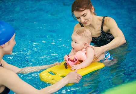 Swimming instructor teaching and helping little baby floating in blue water using auxiliary swimming tools for protection. Family healthy active lifestyle, early development, happy childhood concept