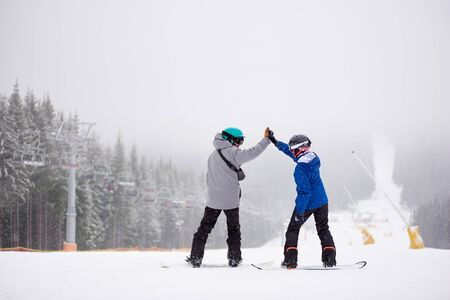 Back view of couple of snowboarders with hands up standing on ski slope. Male and female giving high five to each other before riding down on snowboard. Monochrome winter snowfall view