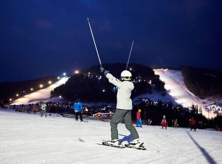 Back view of female skier rejoicing lifting hands up with ski poles. Happy ending of active sports skiing winter day at ski resort. On background mountains with ski slopes under dark blue sky. 版權商用圖片
