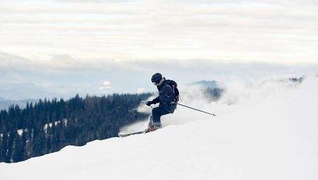 Side view of freerider skier descending from mountain in deep white snow powder. Popular kind of winter sport. Skier on slope. Concept of extreme amateur sport. Mountains view. Grey sky on background.