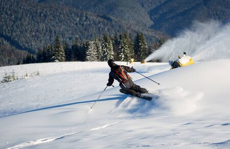 Back view of man skiing on slope with fresh new powder snow. Artificial snowfall in sunny day. Electric snow gun machine. Ski lesson in skiing school. Scenic wooded mountains on background.