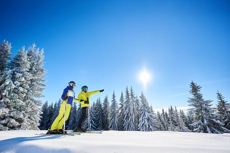 Friends man and woman in goggles enjoying sunny weather on wooded slope. Beautiful winter landscape on background. Recreational activities concept. Bright winter sun on clean blue sky with copy space.