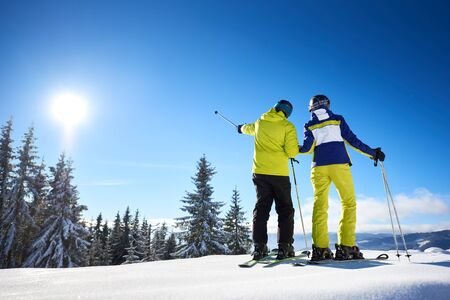 Male skier showing with ski poles on sun high in blue sky over winter mountains. Back view of couple resting during skiing on sunny winter day. Picturesque view of nature in mountains. Copy space.