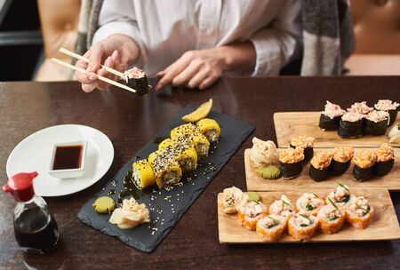 Four course lunch on special offer in luxury oriental restaurant. Elegant female client wrapped in blanket tasty delicious sushi set with seafood. Woman eating Japanese dish using food sticks.