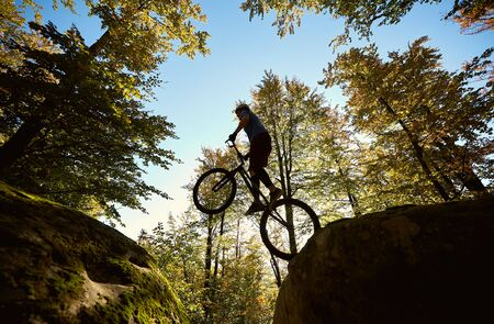 Young sportsman jumping on trial bike, professional cyclist making acrobatic stunt between two big boulders in the forest on summer sunny day. Concept of extreme sport active lifestyle