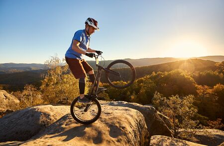 Athletic cyclist balancing on back wheel on trial bike. Sportsman biker making acrobatic trick on the edge of big boulder on the top of mountain at sunset. Concept of extreme sport active lifestyle