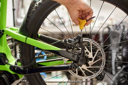 Cropped shot of male mechanic working in bicycle repair shop, bicyclist fixing bike brakes using special tool Imagens
