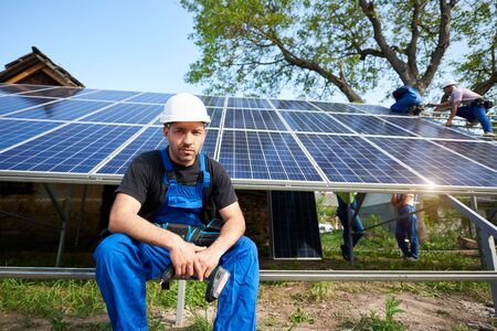 Portrait of successful engineer technician with electrical screwdriver looking in camera, sitting in front of almost finished solar panel photo voltaic system with team of workers on high platform. Archivio Fotografico