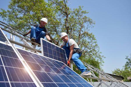 Due giovani tecnici che montano un pannello solare fotovoltaico pesante su una piattaforma in acciaio alta su sfondo verde dell'albero. Installazione del sistema fotovoltaico esterno del pannello solare, concetto di lavoro pericoloso. Archivio Fotografico