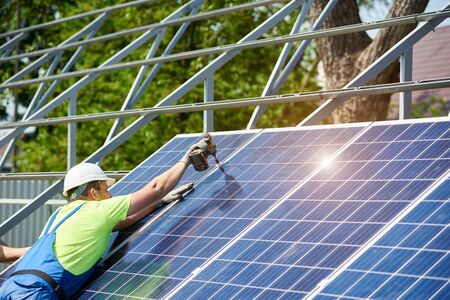 Professional technician working with screwdriver installing shiny solar photo voltaic panel to metal platform system on summer rural landscape and blue sky copy space background.
