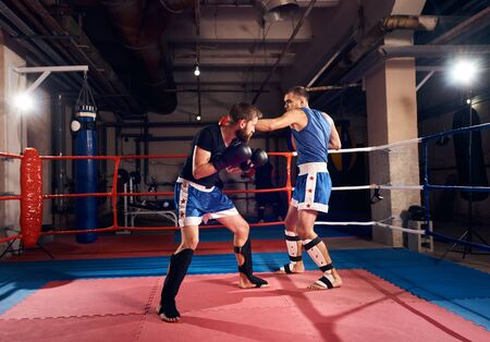 Two strong fighters practicing kickboxing, fighting in the ring at the health club