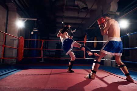 Two aggressive boxers training kickboxing in the ring at the sport club