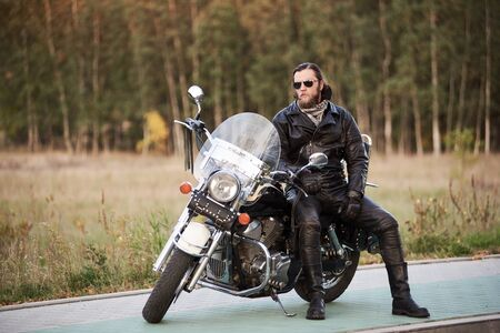 Bearded motorcyclist in black leather clothing and dark sunglasses sitting on cruiser bike on clean paved roadside in the evening, on background of vintage trees golden bokeh foliage.