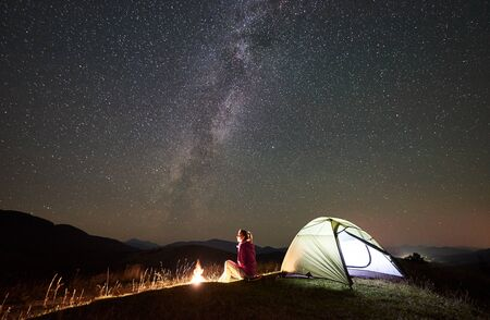 Female hiker relaxing at summer night camping in mountains beside bonfire, glowing tourist tent. Young woman backpacker enjoying view of night sky full of stars and Milky way. Travel adventure concept 版權商用圖片