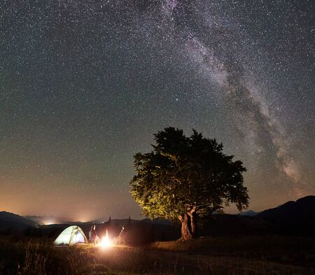 Happy family tourists having a rest at summer night camping in the mountains. Young man and woman sitting on chairs beside campfire, tent and big tree under starry sky full of stars and Milky way. 版權商用圖片