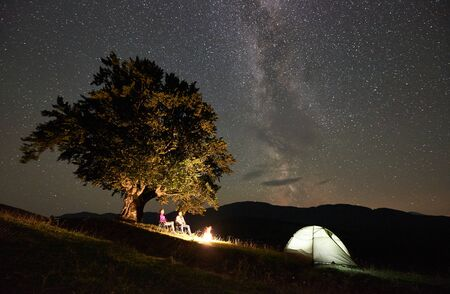 Happy couple hikers relaxing at summer night camping in mountains. Man and woman sitting on chairs beside campfire, tourist illuminated tent under big tree and starry sky full of stars and Milky way.
