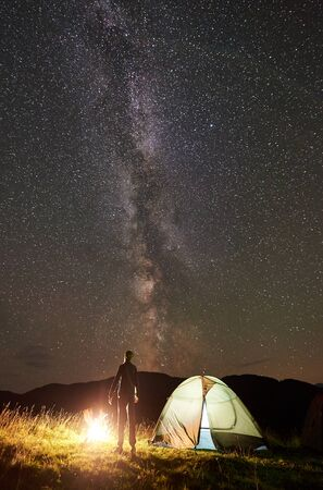 Back view of young man tourist resting at campfire beside camping and glowing tourist tent, enjoying view of night sky full of stars and Milky way. Vertical shot