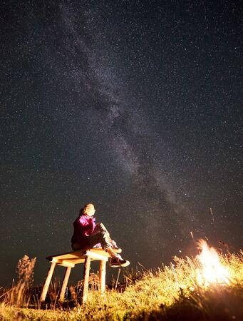 Young female hiker relaxing at summer night camping in the mountains. Happy woman sitting on a bench beside campfire, enjoying view of night sky full of stars and Milky way. Tourism lifestyle concept 版權商用圖片