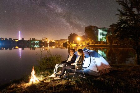 Night camping on lake shore. Man and woman sitting on chairs near tent campfire, enjoying beautiful view of night sky full of stars and Milky way, city lights on background. Outdoor lifestyle concept