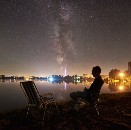 Silhouette of male tourist having a rest on lake shore, sitting on chair near another empty chair, enjoying night sky full of stars and Milky way, quiet water surface, luminous town on background.