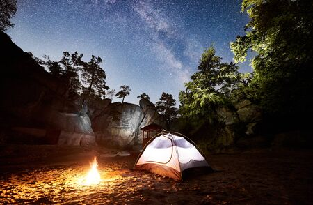 Camping at summer night near mountain rocks. Glowing tourist tent and bonfire under wonderful night sky full of stars and Milky way. On the background beautiful starry sky, big boulders and trees