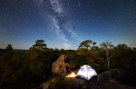 Camping at summer night on rocky mountain. White tourist tent and bonfire under magical night sky full of stars and Milky way. On the background beautiful starry sky, big boulders and trees