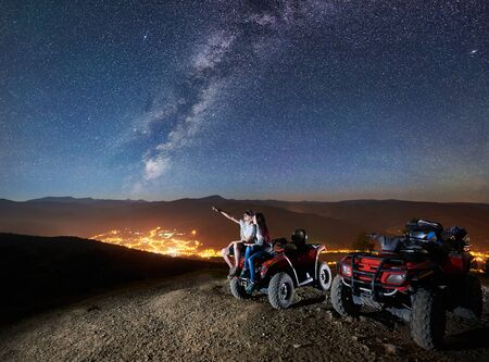 Happy couple man and woman trevelers sitting together on atv quad motorbike on the top of mountain. Man pointing at beautiful night sky full of stars, Milky way, luminous city on background