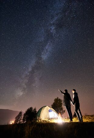 Young couple tourists having a rest at campfire near glowing tent. Woman pointing at amazing night sky full of stars and Milky way. On the background beautiful starry sky, mountains and luminous town 版權商用圖片