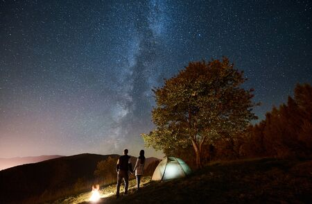 Rear view of happy couple tourists standing at bonfire near glowing tent, holding hands under amazing night sky full of stars and Milky way. On the background starry sky, mountains and big tree Stock Photo