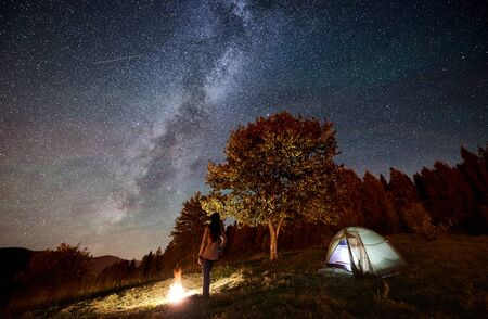 Back view of woman tourist resting at campfire beside camping and illuminated tourist tent, enjoying view of night sky full of stars and Milky way. On background starry sky, mountains and big tree