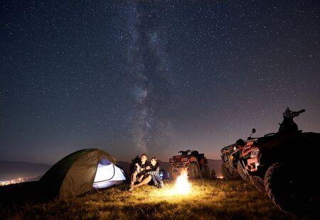Happy couple man and woman trevelers sitting near tourist tent, burning campfire, three atv quad motorbikes on the top of mountain, enjoying beautiful view of night sky full of stars and Milky way 版權商用圖片