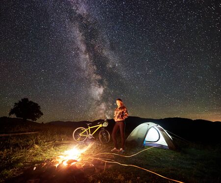 Young woman cyclist having a rest at night camping near burning campfire, illuminated tourist tent, mountain bicycle under amazing beautiful evening sky full of stars and Milky way. Astrophotography